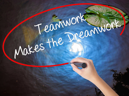 succession: Woman Hand Writing Teamwork Makes the Dreamwork with marker over transparent board. Isolated on nature. Business concept. Stock Photo