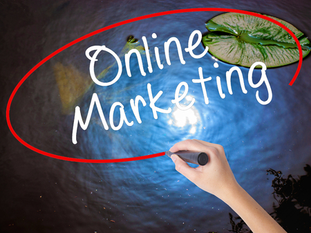 Woman Hand Writing Online Marketing with marker over transparent board. Isolated on nature. Business concept. Stock Image