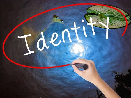 Woman Hand Writing Identity with marker over transparent board. Isolated on nature. Business concept. Stock Image