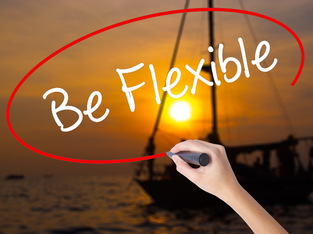 Woman Hand Writing Be Flexible with a marker over transparent board. Isolated on Sunset Boat. Business concept. Stock Photo