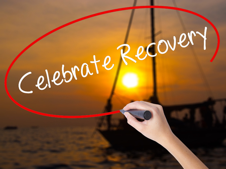 Woman Hand Writing Celebrate Recovery with a marker over transparent board. Isolated on Sunset Boat. Business, technology, internet concept.