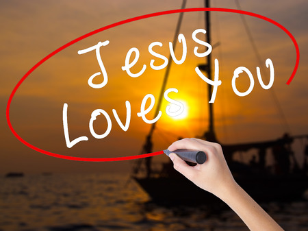 testament schreiben: Woman Hand Writing Jesus Loves You with a marker over transparent board. Isolated on Sunset Boat. Religion, technology, internet concept. Stock Image