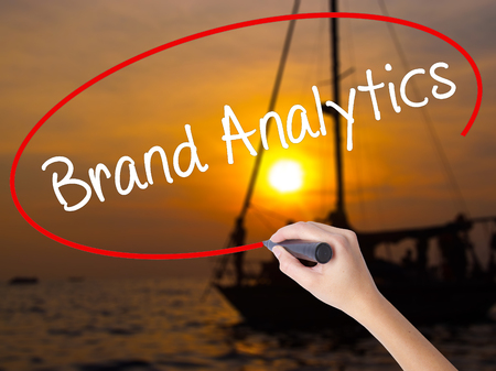 brand monitoring: Woman Hand Writing Brand Analytics with a marker over transparent board. Isolated on Sunset Boat. Business concept. Stock Photo