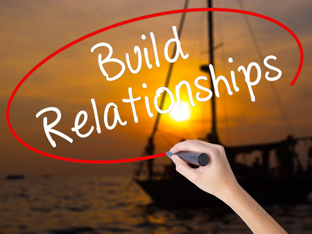 Woman Hand Writing Build Relationships with a marker over transparent board. Isolated on Sunset Boat. Business, technology, internet concept. Stock Image Stock Photo