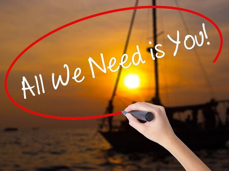 Woman Hand Writing  All We Need is You!  with a marker over transparent board. Isolated on Sunset Boat. Business concept. Stock Photo