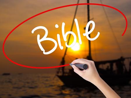 vangelo aperto: Donna Mano scrittura della Bibbia con un pennarello sopra bordo trasparente. Isolato su tramonto Barca. Concetto di affari. Archivi fotografici Archivio Fotografico