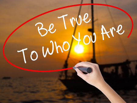 true self: Woman Hand Writing Be True To Who You Are with a marker over transparent board. Isolated on Sunset Boat. Business concept. Stock Photo