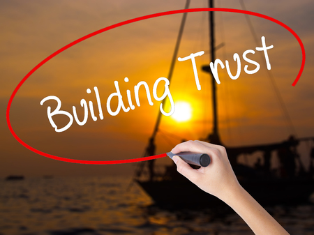building trust: Woman Hand Writing Building Trust with a marker over transparent board. Isolated on Sunset Boat. Business concept. Stock Photo Stock Photo