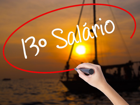 Woman Hand Writing 13 Salary (13o salario In Portuguese)  with a marker over transparent board. Isolated on Sunset Boat. Business concept. Stock Photo Stock Photo