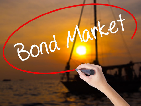 Woman Hand Writing Bond Market with a marker over transparent board. Isolated on Sunset Boat. Business concept. Stock Photo