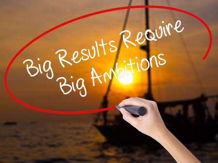 Woman Hand Writing Big Results Require Big Ambitions with a marker over transparent board. Isolated on Sunset Boat. Business concept. Stock Photo Stock Photo