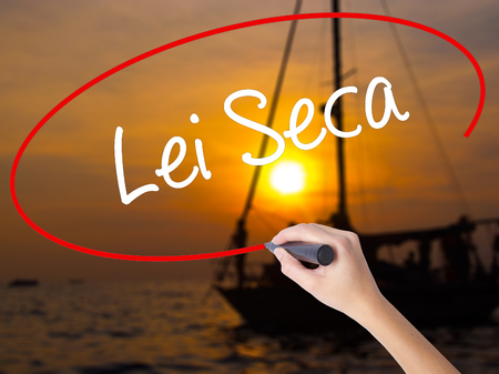 Woman Hand Writing Lei Seca (Prohibition Alcohol Law n Portuguese) with a marker over transparent board. Isolated on Sunset Boat. Business concept. Stock Photo