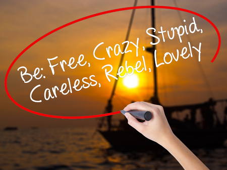 Woman Hand Writing Be: Free, Crazy, Stupid, Careless, Rebel, Lovely with a marker over transparent board. Isolated on Sunset Boat. Business concept. Stock Photo Stock Photo