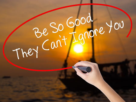 competent: Woman Hand Writing Be So Good They Cant Ignore You with a marker over transparent board. Isolated on Sunset Boat. Business concept. Stock Photo