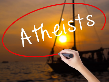 disbelieve: Woman Hand Writing Atheists with a marker over transparent board. Isolated on Sunset Boat. Business, technology, internet concept. Stock Image