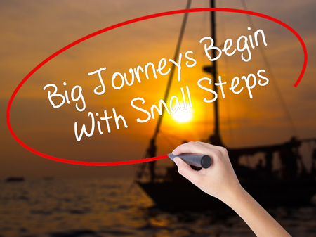 Woman Hand Writing Big Journeys Begin With Small Steps  with a marker over transparent board. Isolated on Sunset Boat. Business concept. Stock Photo