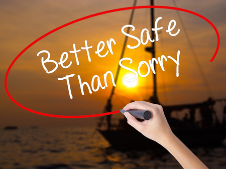 better safe than sorry: Woman Hand Writing Better Safe Than Sorry with a marker over transparent board. Isolated on Sunset Boat. Business concept. Stock Photo