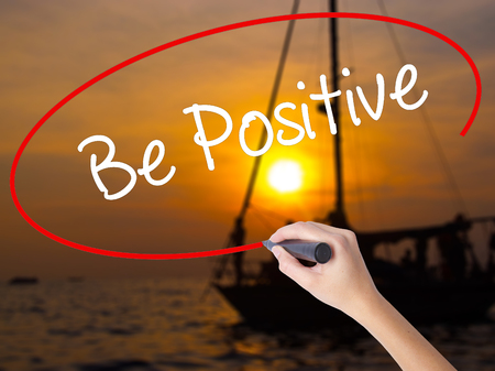 Woman Hand Writing Be Positive  with a marker over transparent board. Isolated on Sunset Boat. Business concept. Stock Photo