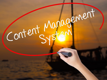 Woman Hand Writing Content Management System  with a marker over transparent board. Isolated on Sunset Boat. Business concept. Stock Photo