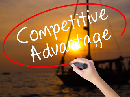 Woman Hand Writing Competitive Advantage with a marker over transparent board. Isolated on Sunset Boat. Business, technology, internet concept. Stock Image