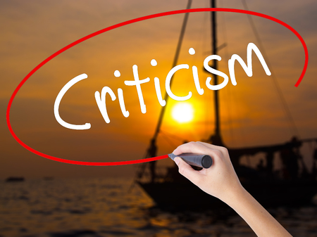 criticism: Woman Hand Writing Criticism with a marker over transparent board. Isolated on Sunset Boat. Business concept. Stock Photo
