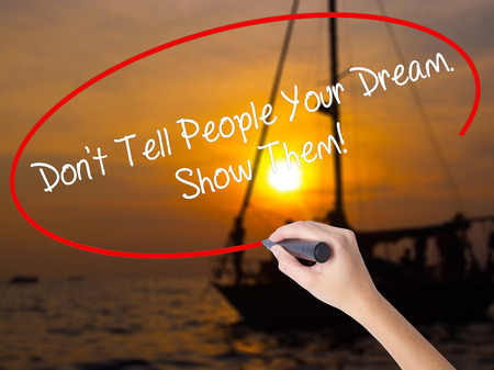 Woman Hand Writing Dont Tell People Your Dream. Show Them! with a marker over transparent board. Isolated on Sunset Boat. Business, technology, internet concept. Standard-Bild
