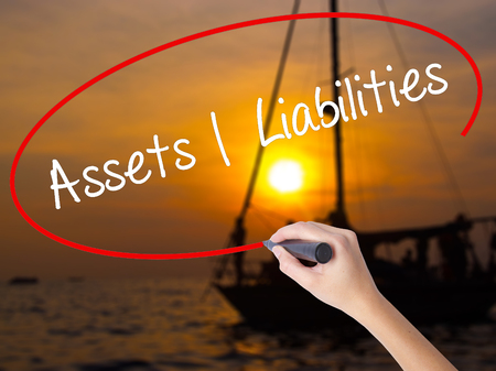 Woman Hand Writing Assets Liabilities with a marker over transparent board. Isolated on Sunset Boat. Business concept. Stock Photo