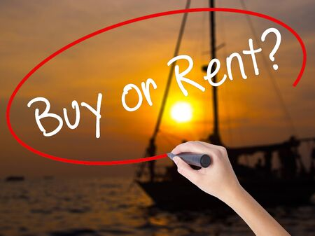 Woman Hand Writing Buy or Rent? with a marker over transparent board. Isolated on Sunset Boat. Business, technology, internet concept. Stock Image