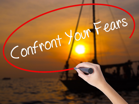 unafraid: Woman Hand Writing Confront Your Fears with a marker over transparent board. Isolated on Sunset Boat. Business concept. Stock Photo