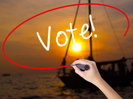 conscientious: Woman Hand Writing Vote! with a marker over transparent board. Isolated on Sunset Boat. Business concept. Stock Photo