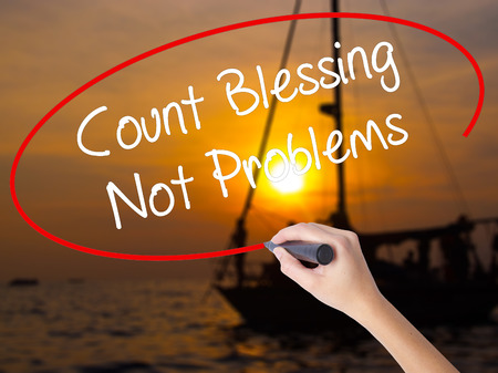 preachment: Woman Hand Writing Count Blessing Not Problems with a marker over transparent board. Isolated on Sunset Boat. Business concept. Stock Photo