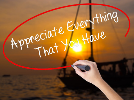 indebtedness: Woman Hand Writing Appreciate Everything That You Have with a marker over transparent board. Isolated on Sunset Boat. Business concept. Stock Photo