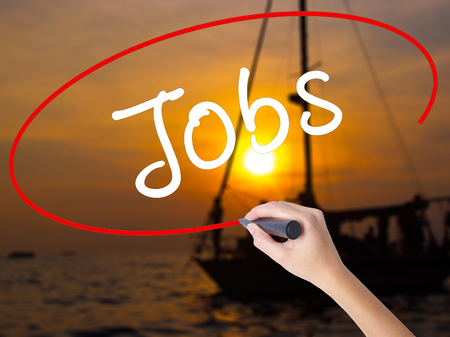 joblessness: Woman Hand Writing Jobs with a marker over transparent board. Isolated on Sunset Boat. Business, technology, internet concept. Stock Image