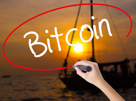 ltc: Woman Hand Writing Bitcoin with a marker over transparent board. Isolated on Sunset Boat. Business concept. Stock Photo