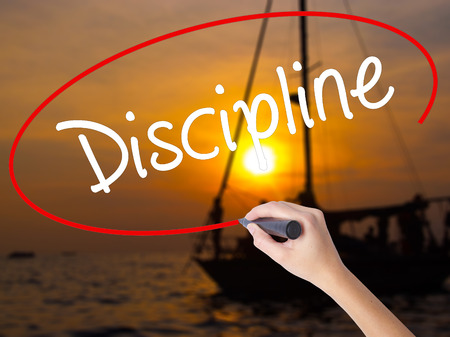 Woman Hand Writing Discipline with a marker over transparent board. Isolated on Sunset Boat. Business concept. Stock Photo