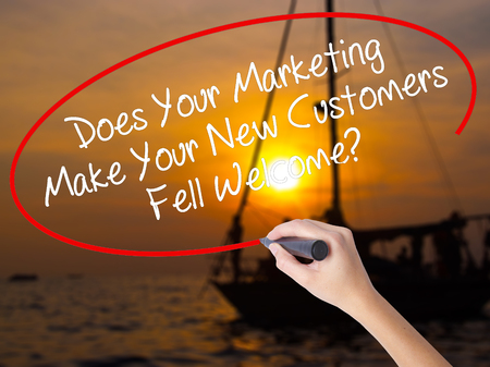 Woman Hand Writing Does Your Marketing Make Your New Customers Fell Welcome?  with a marker over transparent board. Isolated on Sunset Boat. Business concept. Stock Photo Stock Photo