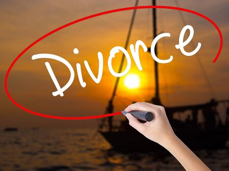 ex wife: Woman Hand Writing Divorce  with a marker over transparent board. Isolated on Sunset Boat. Business concept. Stock Photo