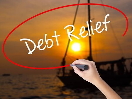 trouble free: Woman Hand Writing Debt Relief with a marker over transparent board. Isolated on Sunset Boat. Business concept. Stock Photo