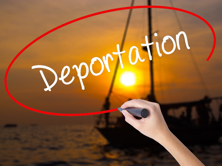 naturalization: Woman Hand Writing Deportation  with a marker over transparent board. Isolated on Sunset Boat. Business concept. Stock Photo Stock Photo
