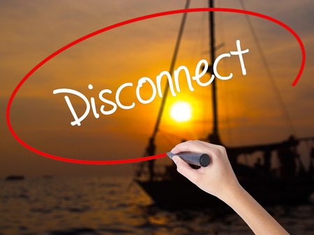 Woman Hand Writing Disconnect with a marker over transparent board. Isolated on Sunset Boat. Business concept. Stock Photo