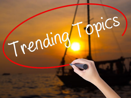 business trending: Woman Hand Writing Trending Topics with a marker over transparent board. Isolated on Sunset Boat. Business concept. Stock Photo