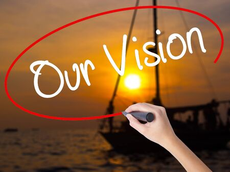 Woman Hand Writing Our Vision with a marker over transparent board. Isolated on Sunset Boat. Business concept. Stock Photo