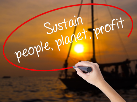 Woman Hand Writing Sustain, people, planet, profit with a marker over transparent board. Isolated on Sunset Boat. Business concept. Stock Photo