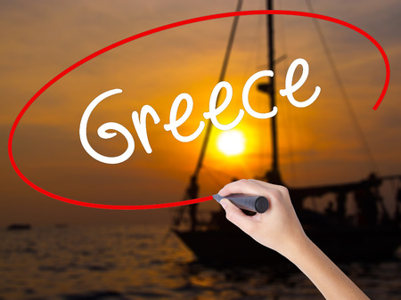Woman Hand Writing Greece  with a marker over transparent board. Isolated on Sunset Boat. Business concept. Stock Photo