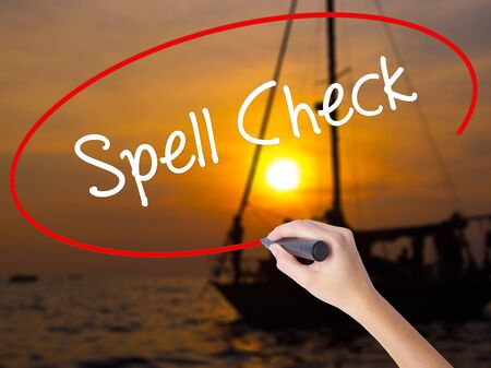 revise: Woman Hand Writing Spell Check  with a marker over transparent board. Isolated on Sunset Boat. Business, technology, internet concept. Stock Photo