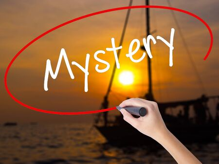 inference: Woman Hand Writing Mystery with a marker over transparent board. Isolated on Sunset Boat. Business concept. Stock Photo Stock Photo