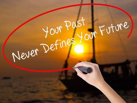 defines: Woman Hand Writing Your Past Never Defines Your Future with a marker over transparent board. Isolated on Sunset Boat. Business concept. Stock Photo Stock Photo