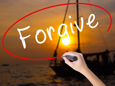 redeeming: Woman Hand Writing Forgive with a marker over transparent board. Isolated on Sunset Boat. Business, technology, internet concept. Stock Image