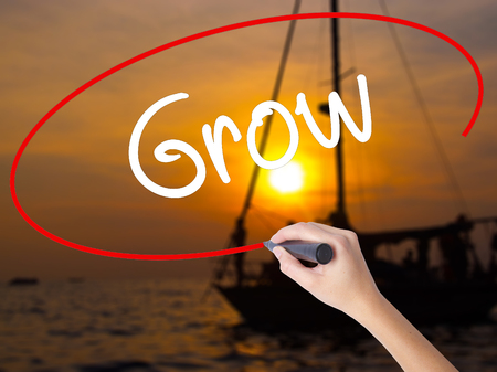 Woman Hand Writing  Grow with a marker over transparent board. Isolated on Sunset Boat. Business concept. Stock Photo