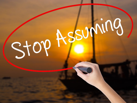 Woman Hand Writing Stop Assuming with a marker over transparent board. Isolated on Sunset Boat. Business concept. Stock Photo